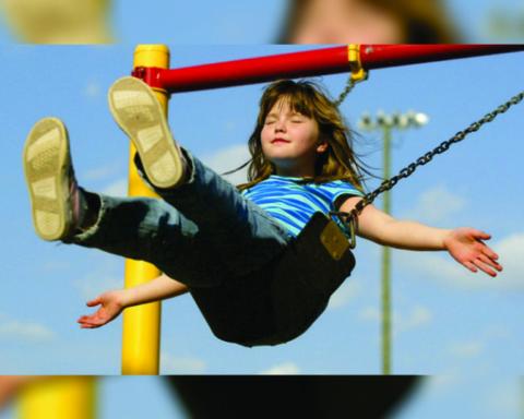 Criança aproveita férias brincando em balanço