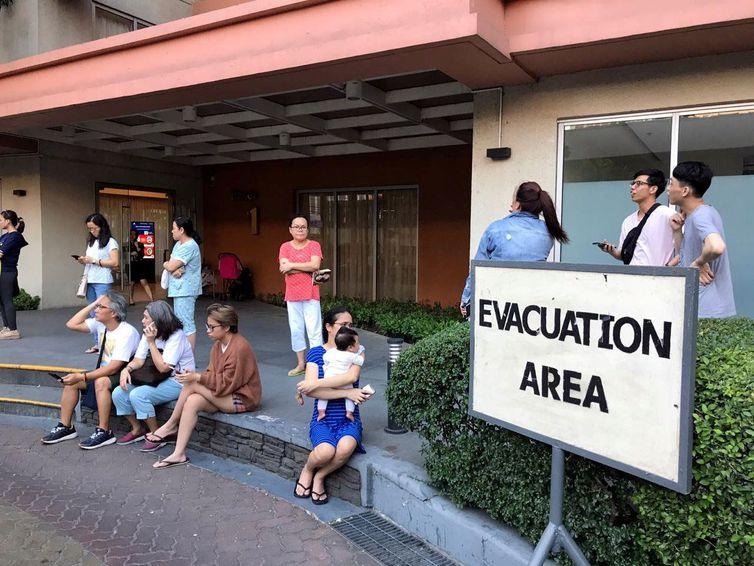 Moradores se sentam do lado de fora depois de serem evacuados do prédio do condomínio após um terremoto na cidade de Makati